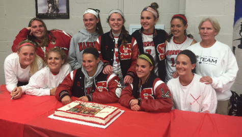 The field hockey seniors and Coach Sharon McLaughlin gather around their cake at the post game celebration. Photo by Addy Schefter.