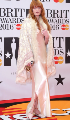 Florence Welch yet again made a brave style choice in a Calvin Klein slip dress that was styled with a Gucci fringe cape and Alexander McQueen clutch. Photo By: Courtesy of the Brit Awards 02 Arena in London