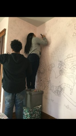 Photo of Jackson outlining her wall with the help of her brother senior Khalil Jackson Photo By:Allure Sapp