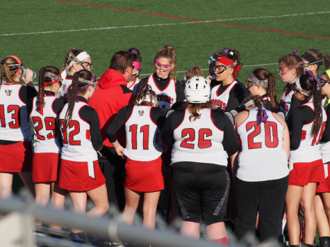The team huddles on the field. Photo by Lisa Miller.
