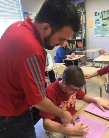 Spanish teacher Nick Schiffgens assists sophomore Justin Feild with an assignment. Photo by Karly Matthews.