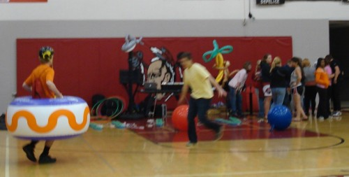 The inflatable bumper game, and students line up in the background for glitter tattoos.