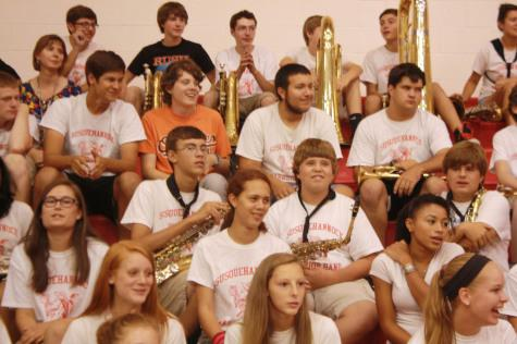 The band watches intently as students compete.