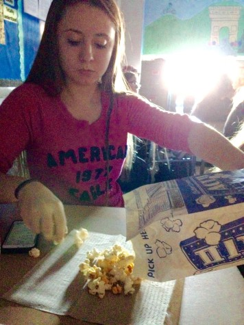 Junior Lexi Manker pours herself some popcorn during the movie.  Photo By: Grace Burns