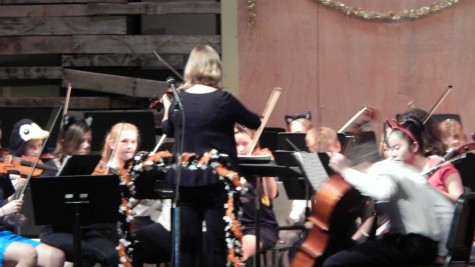 The concert began with the middle school orchestra performing their pieces. The concert master shown here is helping the orchestra tune their instruments so that they can be in tune for their pieces.