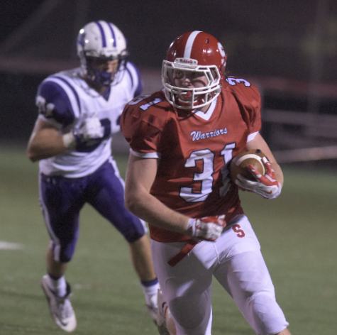 Senior Kevin Clapp carries the ball past a Northern defender. Photo by Lifetouch.