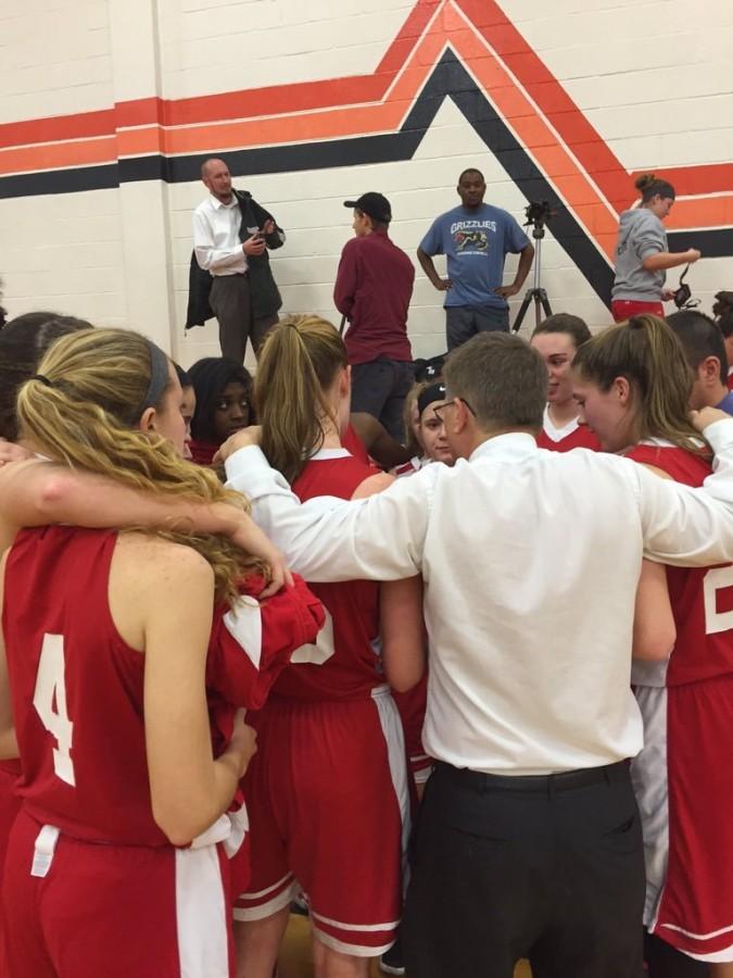 Girls basketball huddles during a timeout