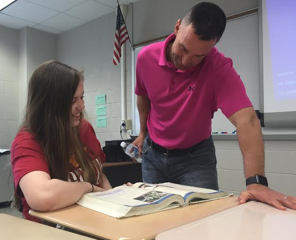 Social studies teacher Kevin Lawrence looks over the textbook with senior Laura Willem. Photo by Karly Matthews.
