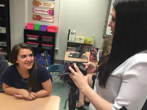 Senior Camryn Burke and yearbook adviser Jessica Beste look over photos. Photo by Karly Matthews.