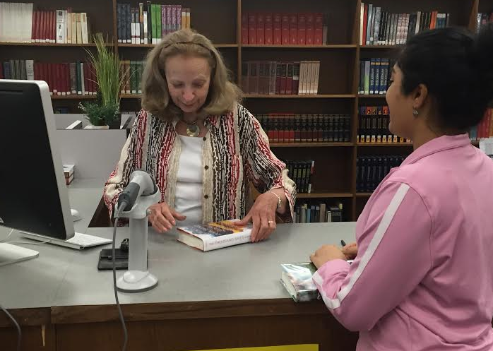May kindly suggests a novel for senior Vaish Kandala before helping her check it out. Photo by the author.