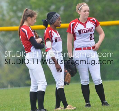 Mackenzie Gibson (pictured far right) chats with fellow outfielders before the inning starts. Photo By: Studio West Photography