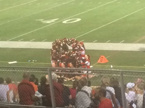 """The cheerleaders spell out an """"S"""" to support the football team."""