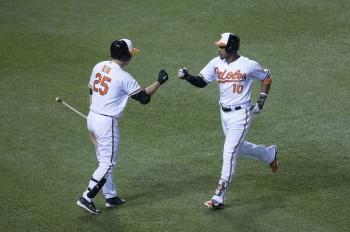 Adam Jones and Hyun Soo Kim celebrate scoring a run. Photo from Keith Allison.