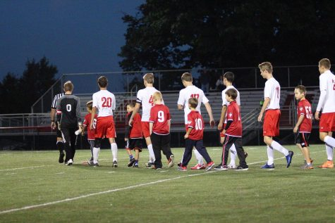 Susky's Varsity starters walk young players to the midfield. Photo by Laurie Kettinger.
