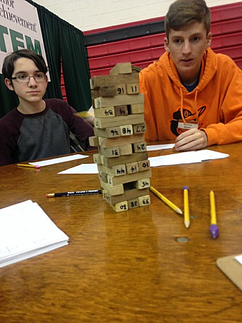 Students worked together to complete different math puzzles. Here, teens solved problems that coordinated with the numbers on the Jenga blocks.