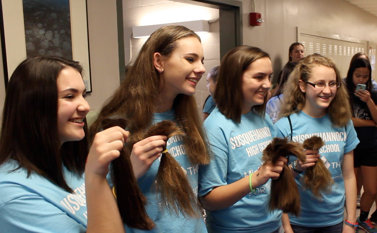 Mini-THON participants show off their new haircuts after donating hair for cancer patients. Photo by Dan McNair.