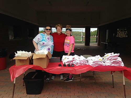 School counselor Evelyn Kabke, science teacher Barbara Nealon and junior Julia McKenzie helped at the sign-in stand to give runners shirts and good bags.