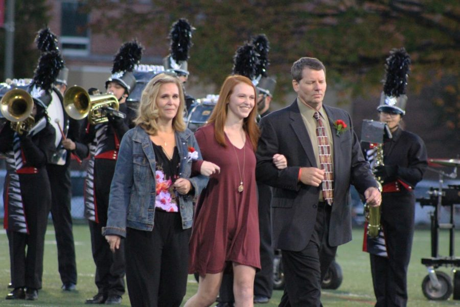 Senior Erin Kaliszak walks with her mother and father before she finds out she has been crowned homecoming queen.