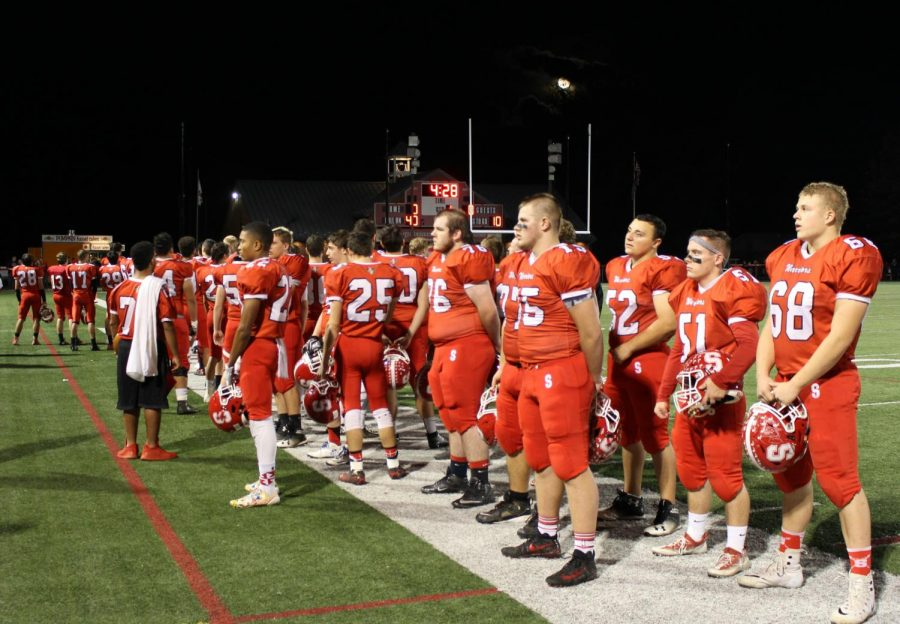 Football players line up along the sideline for the national anthem before the start of the game.