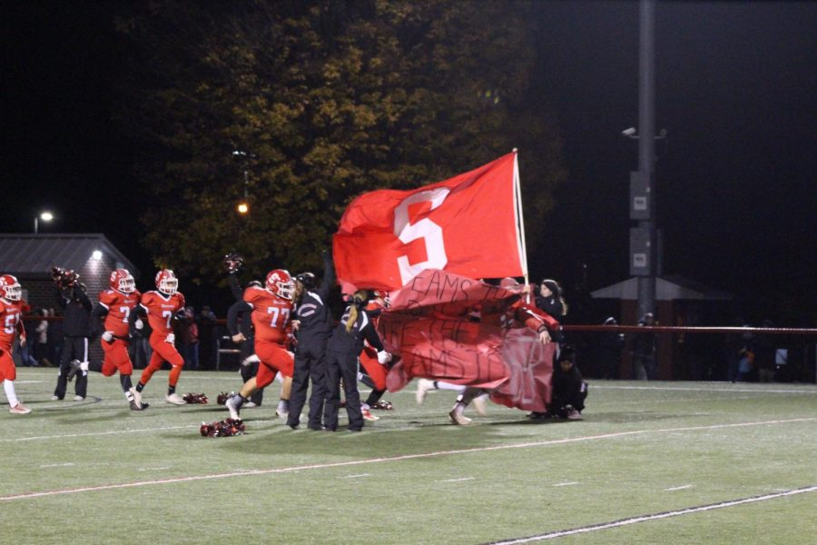 Senior+Brent+Hofler+is+the+first+to+break+through+the+sign%2C+carrying+the+Susquehannock+flag.+