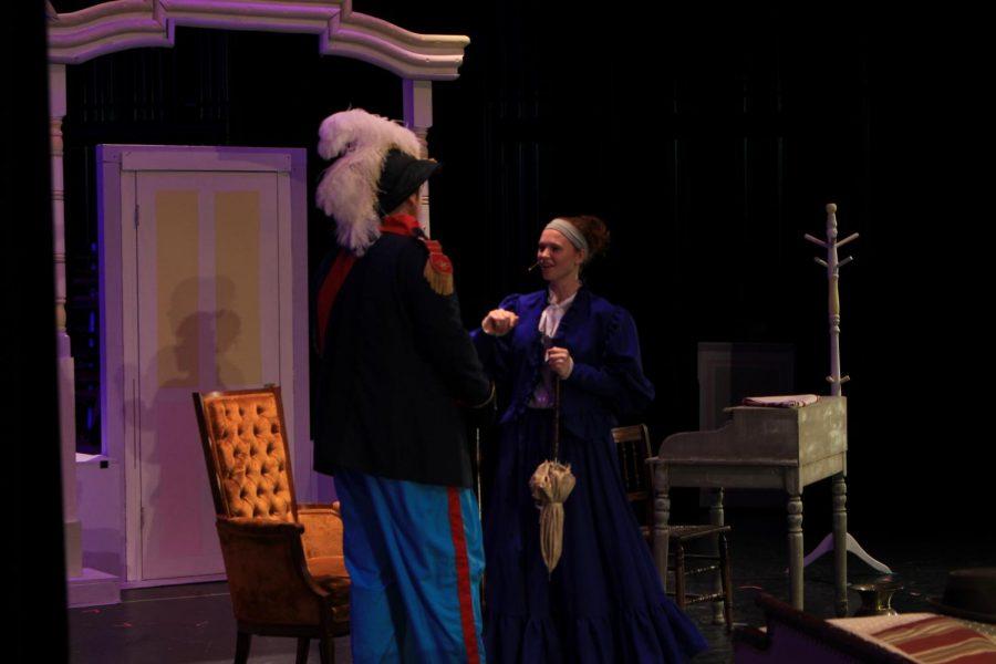 Senior Erin Kaliszak (Mrs. Levi) talks to Vandergelder about his costume.