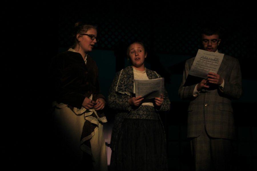 Singing ensemble consisting of  sophomore Kaity Helms, sophomore Jordan Pfteiger, and senior John Katchko performe their song before the beginning of the scene.