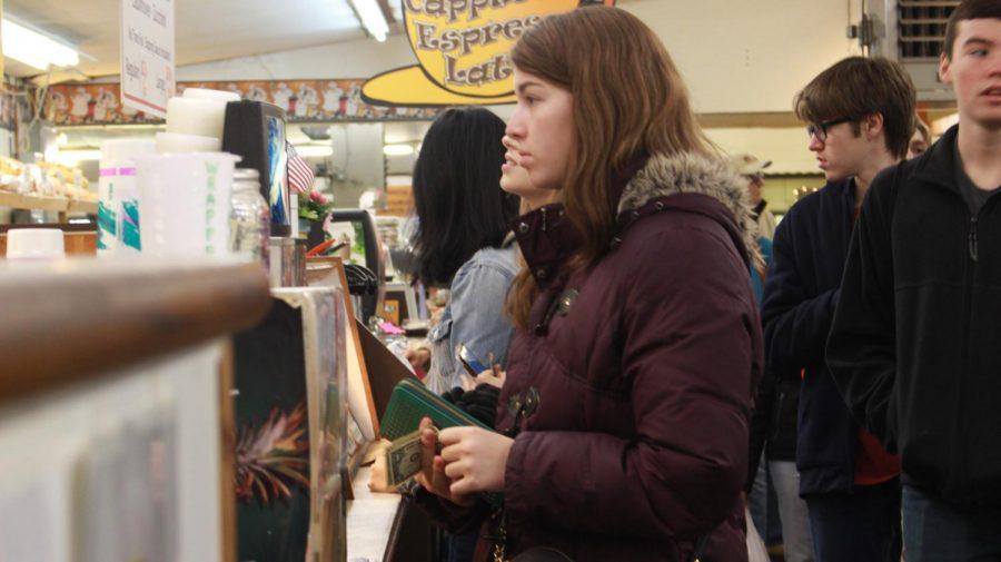 Junior Alex Fabie buys a beverage at the market.