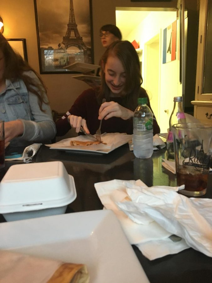 The French club enjoys eating crêpes with each other at 'Rachel's Crepes' during a field trip.