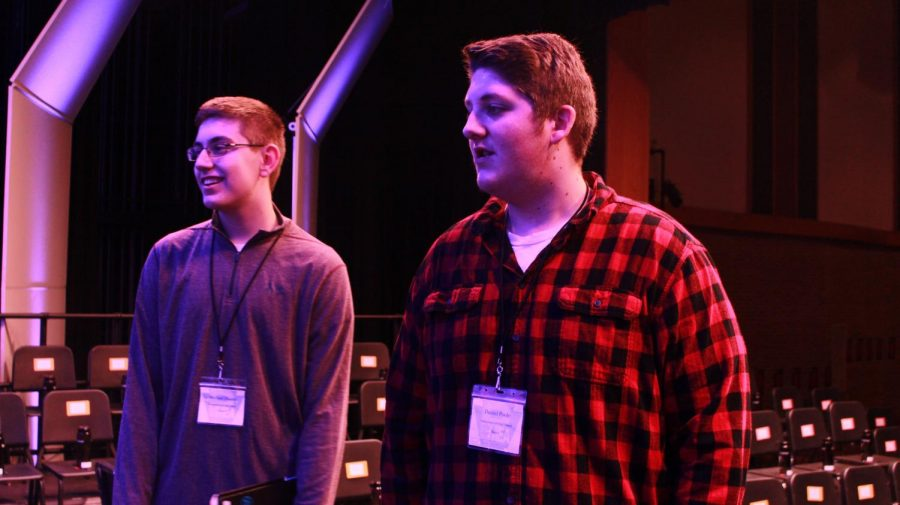 Junior Dan Poole and Sophomore Michael Daiuto search the stage for their chairs before rehearsal.
