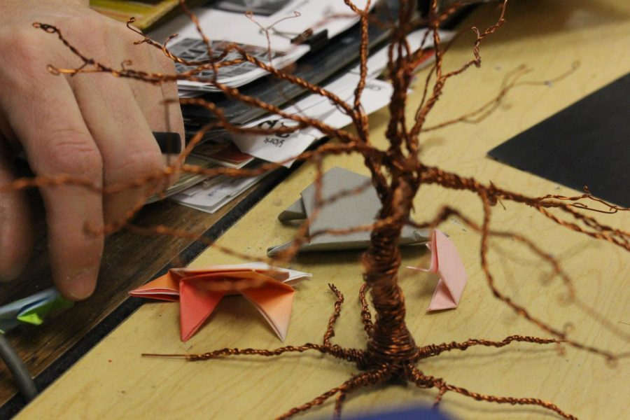 The frogs in the art room live under the wire tree on Myers' desk.