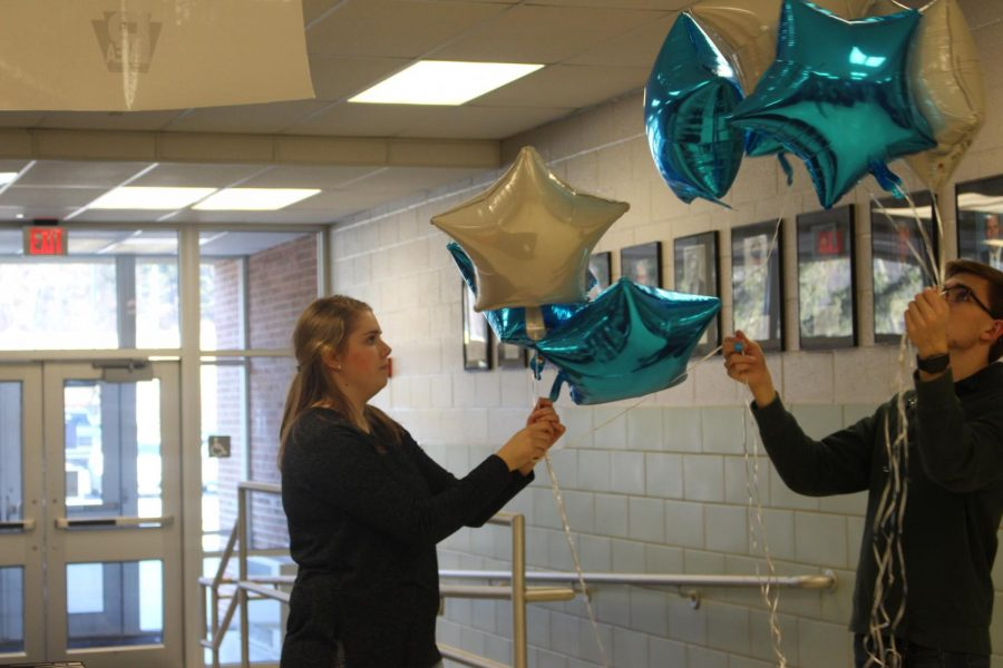 Seniors+Miranda+Shaffer+and+Justin+Feild+decorate+the+Auditorium+Lobby+with+blue+and+silver+balloons+-+the+PMEA+colors.