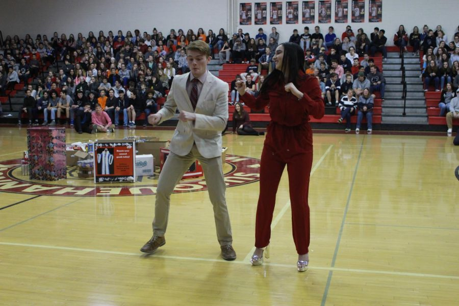 Snow King candidate Hunter Davis and his escort junior Theresa Falzone participate in the decades dance during the pep rally.