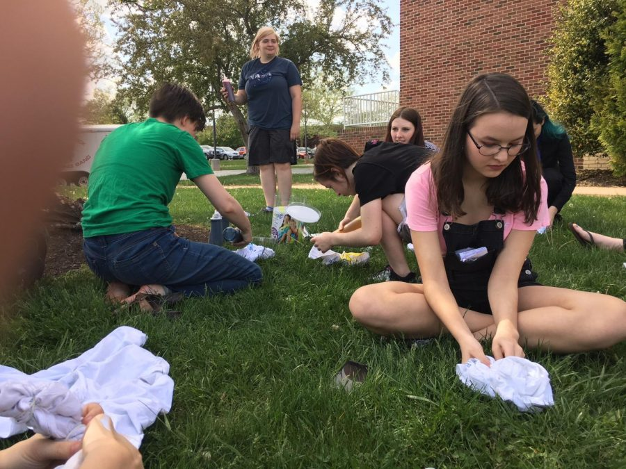Alliance members work on banding their shirts together before adding dye.