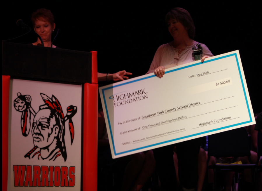 Landis accepts the monetary reward at the annual ceremony.