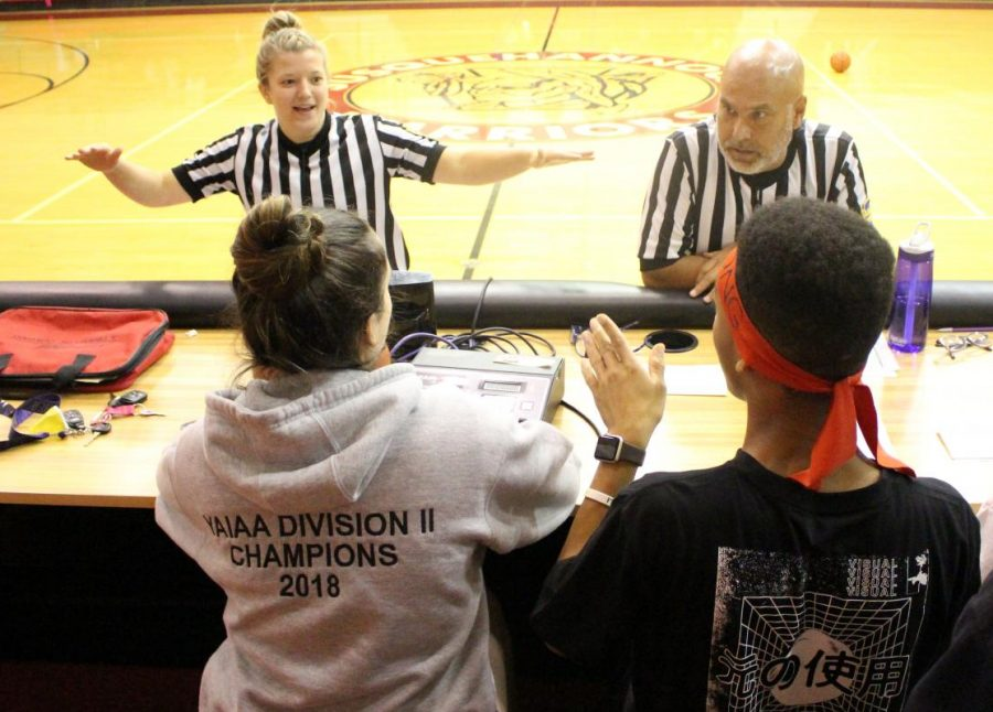 Announcers Michael Boompong and Allie Grothey talk with the refs.