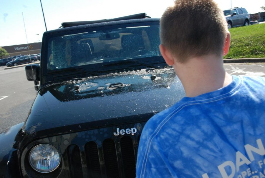 Bobby washes the front of a jeep. Photo by: Ian Achterberg