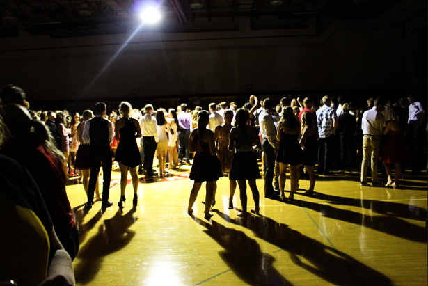 As more students enter, the lights dim, and the music gets louder. A large group of mostly upperclassmen start to gather in the center under the spotlight.