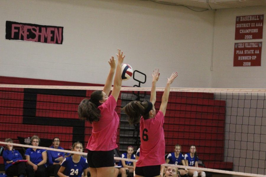 Junior Leah Wilkinson and sophomore Emily Sweitzer go up for the block. Wilkinson is successful with the block and stops the ball in its tracks.  Photo by Stephanie Graffin.