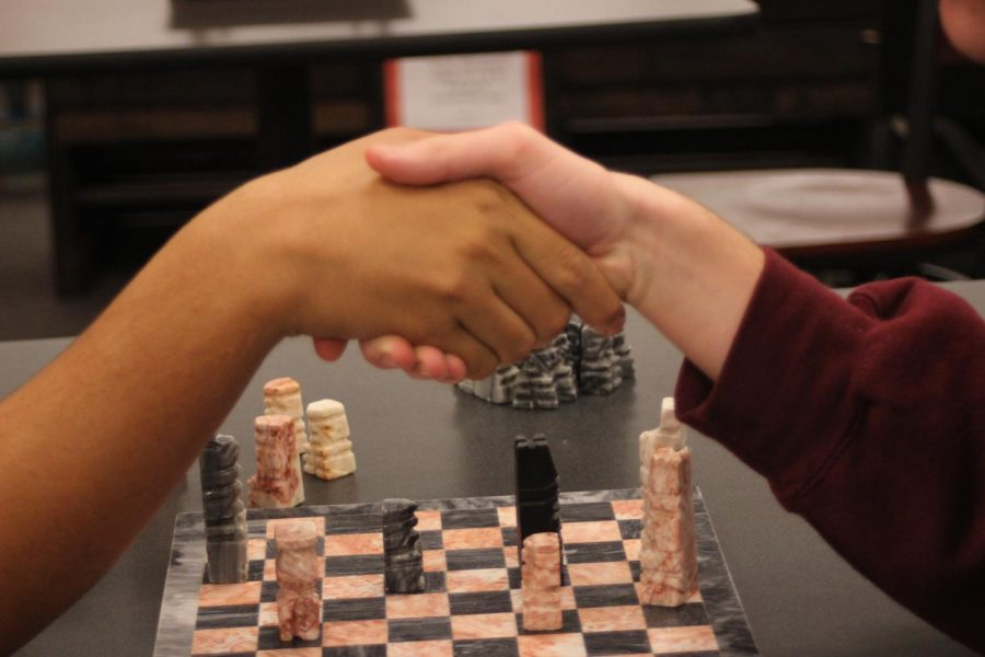 """Junior Nate Binko and sophomore Owen Mechling shake hands after a chess match. Binko said, """"My favorite part about having a chess club is just the bond that I have with other people that like to play chess."""""""