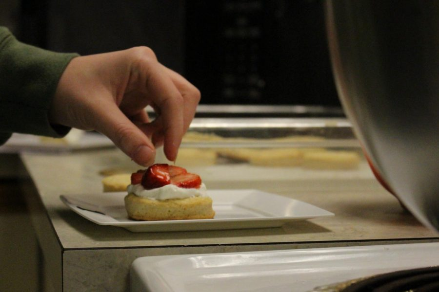 A student perfects the presentation of their dish.