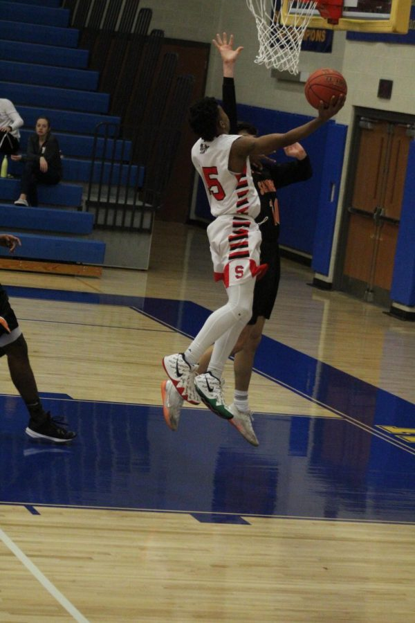 Freshman Jalen Franklin jumps up for the layup, adding two points for the warriors. Franklin has topped 30 points a game multiple times this season.  Photo by Stephanie Graffin