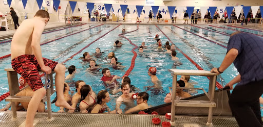 The swim team gathers in the pool at the end of the meet for a final 'huddle.'