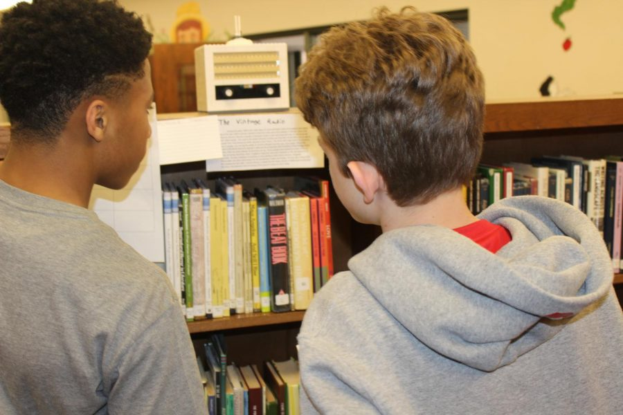 """Freshman Ricky Ferguson and Caleb Bella look at a beautiful recreation of a radio. """"The facts really helped me realize all the cool things people could do back then and all the stuff they could not do with the lack of technology and information they could not do everything we can do right now,"""" said  Tyler Snyder."""