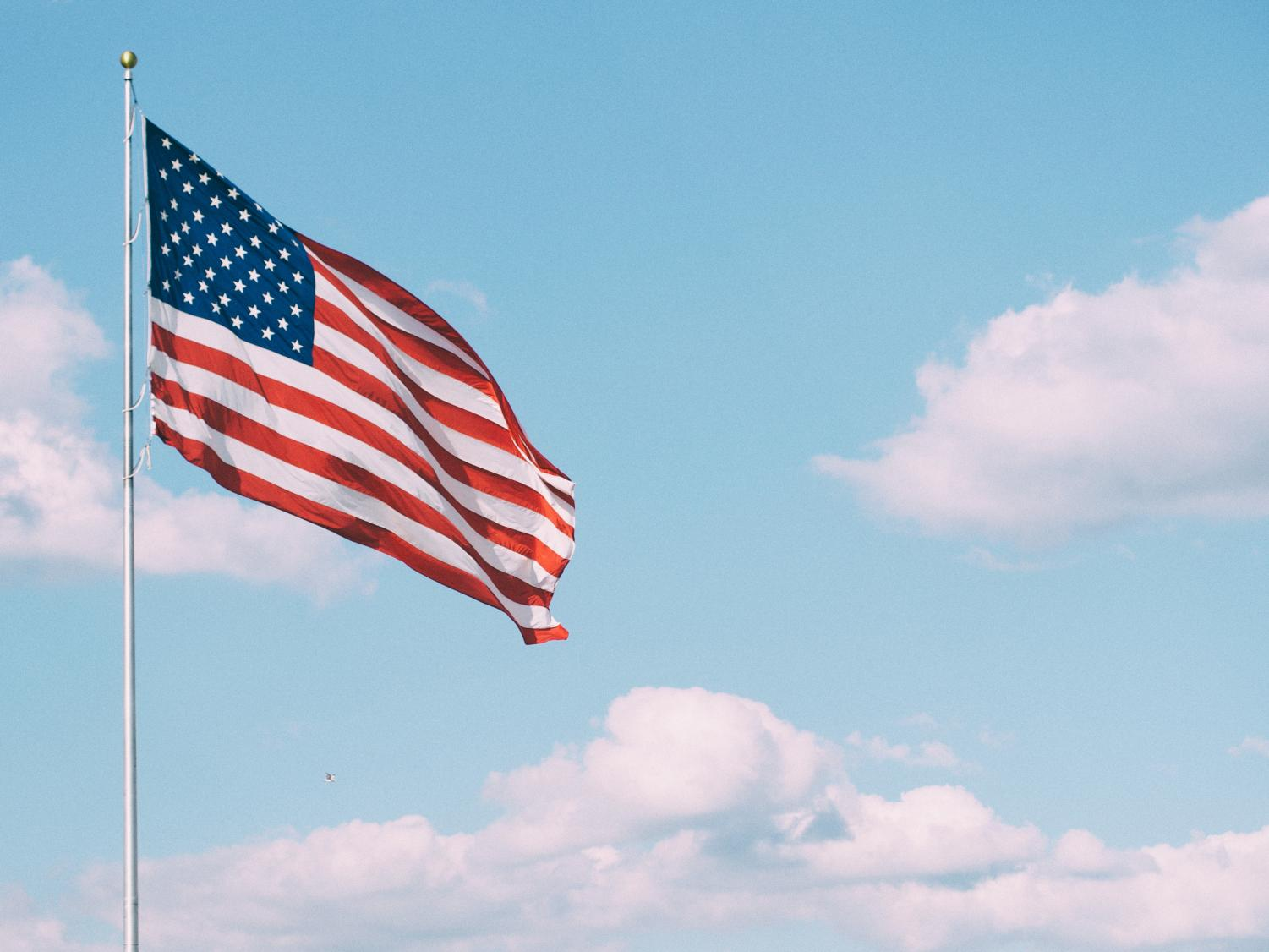 An American flag blows in the wind on a cloudy day. Photograph by Aaron Burden on Unsplash