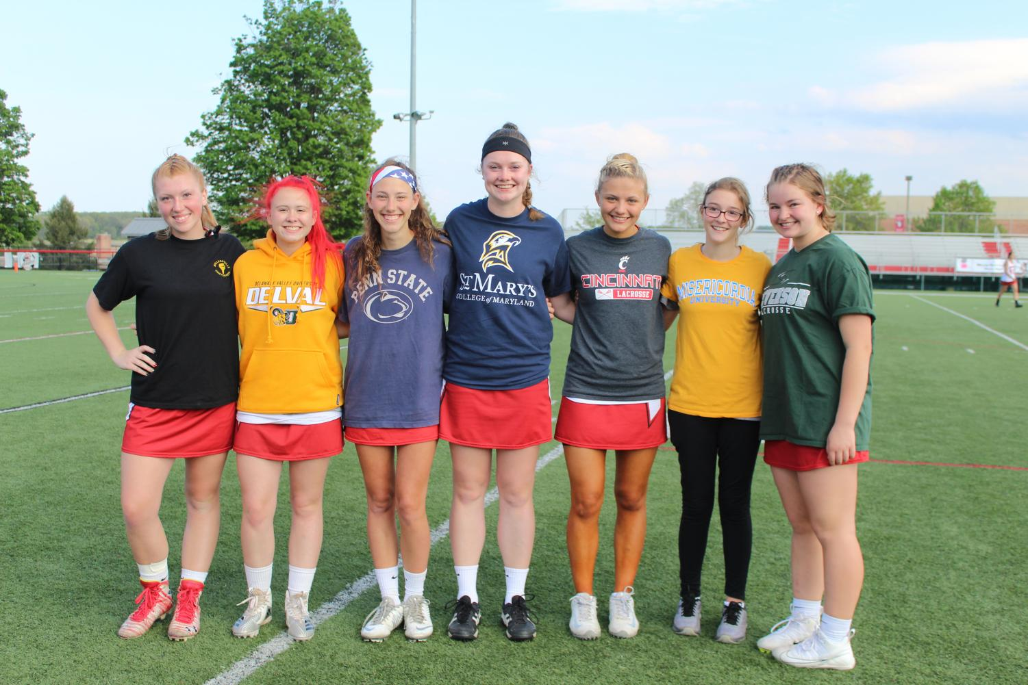 All+seven+seniors+on+the+girls+lacrosse+team+stand+posing+for+a+picture.+Each+girl+wore+a+peice+of+clothing+representing+their+future+college+they+will+be+attending.%0APhotograph+by+Stephanie+Graffin.+