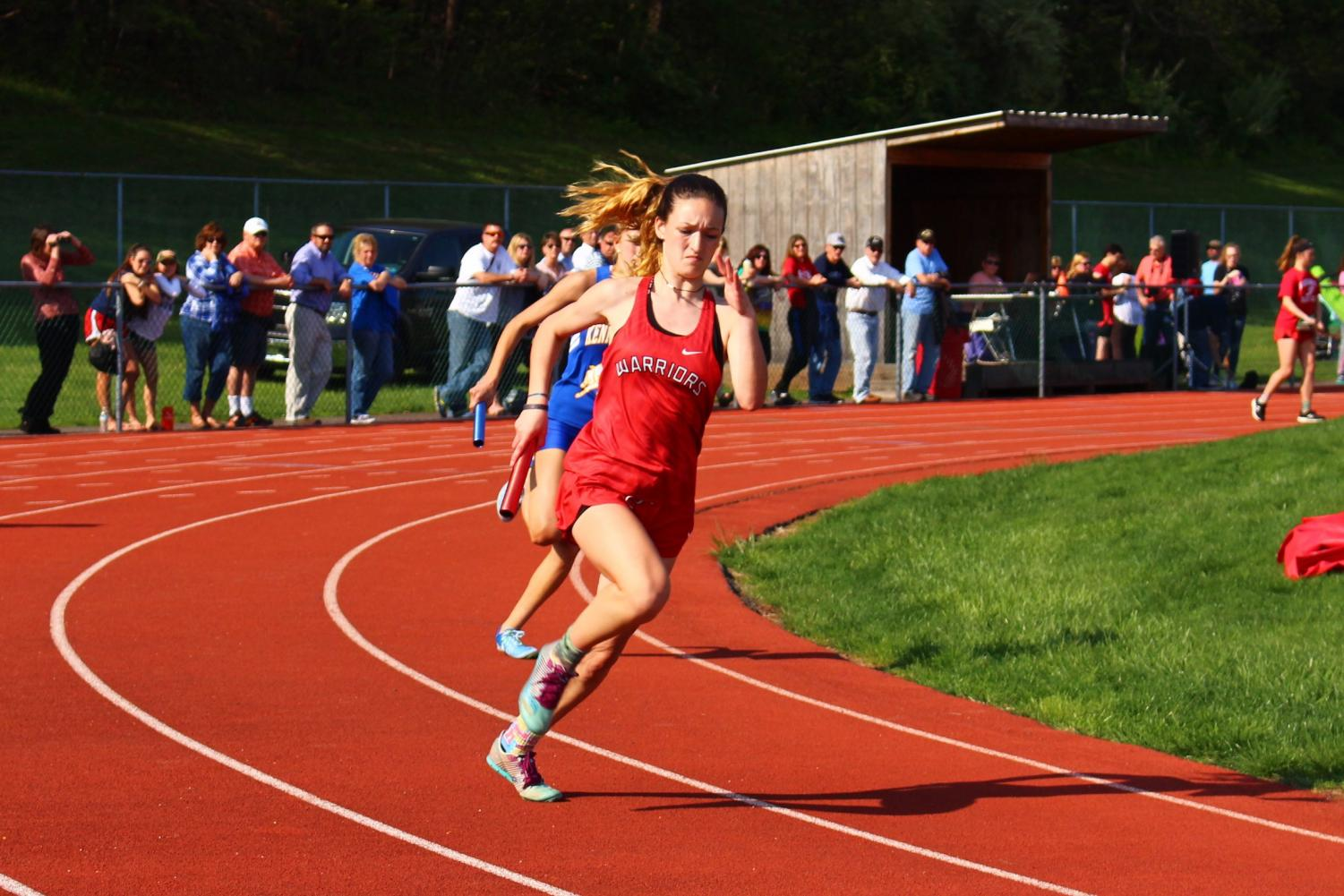 Sophomore+Julia+Bittner+takes+the+turn+in+the+4x100+relay.+In+the+end%2C+both+the+boys+and+girls+teams+for+the+Warriors+beat+the+Rams.+The+boys+score+was+111-39+and+the+girls+score+finished+at+128.5-21.5