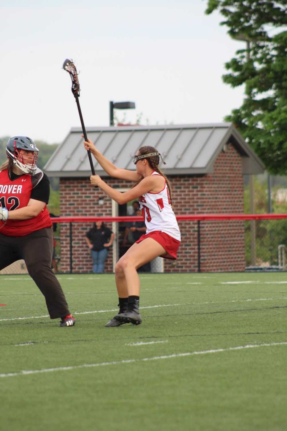 Sophomore+Ariana+Prediger+closely+defends+the+Dover+goalie+attempting+to+clear+the+ball.+Prediger+holds+her+stick+high+to+intercept+any+throw+the+goalie+makes.+Photograph+by+Stephanie+Graffin