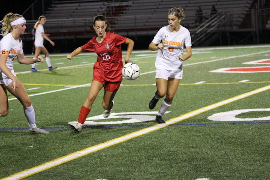 Sophomore Lauren Simpson dribbles up the field after winning the ball from a York Suburban player..