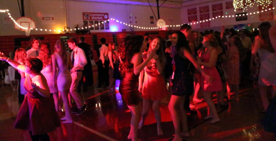 Students dance under the flashing colored lights.