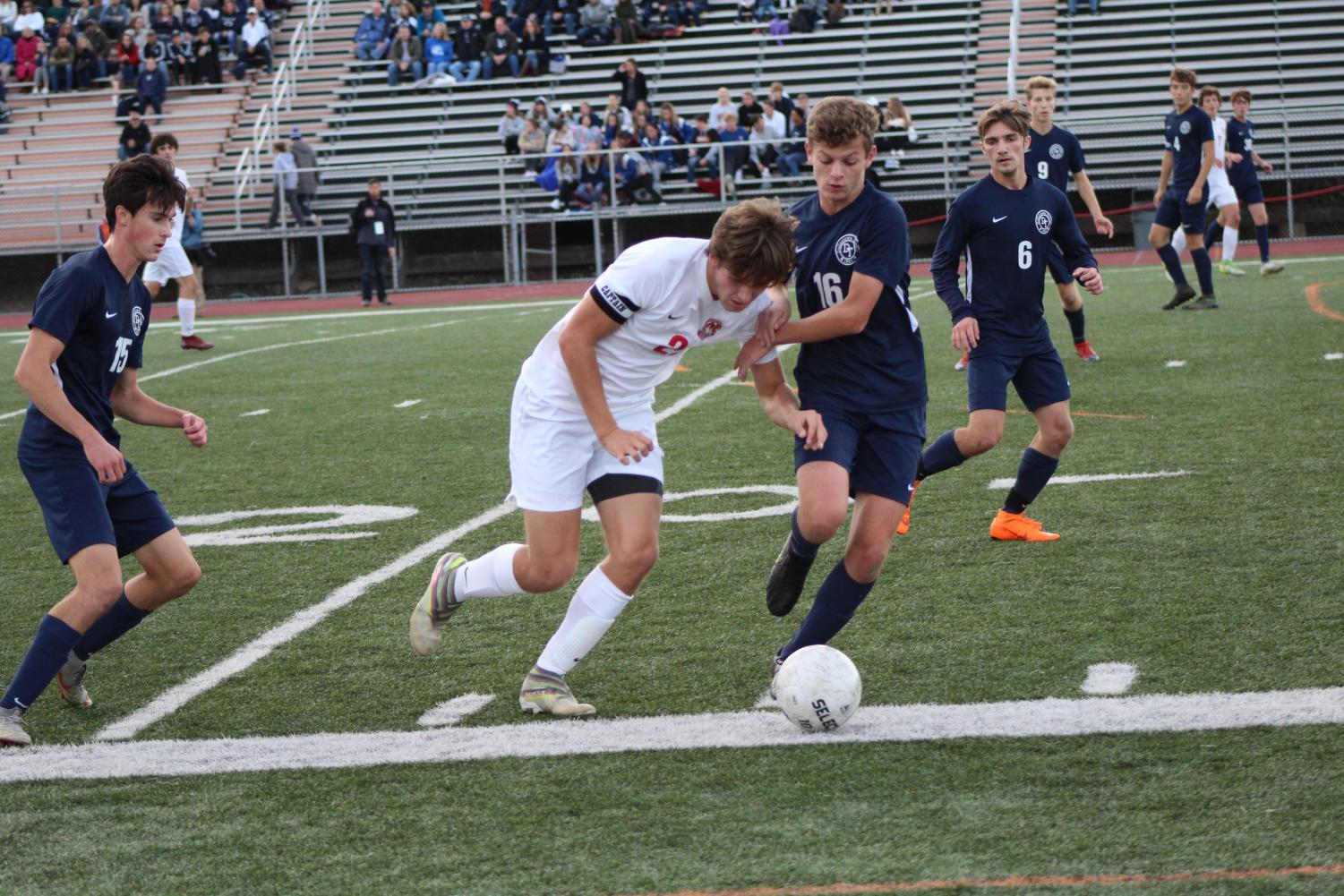 Senior captain Greyson Murray dribbles the ball down the field passing the Wildcat defender.  Photo by Ava Holloway.